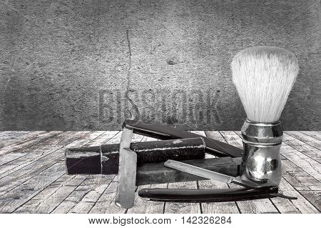 Old razors and shaving brush on background in black and white