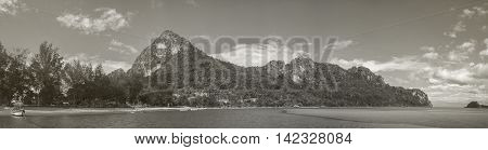 panorama view of long-big mountain and fishing boat laying on a surface of the sea tall pine black and white vintage picture style