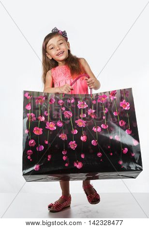 Girl carries a heavy bag, the concept of fashion and shopping