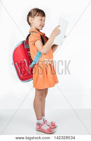 Schoolgirl reading a textbook, while standing on a white background