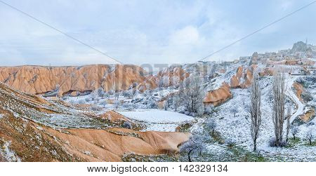 The rose stone valley looks even more colorful adjacent to the snowbound areas Uchisar Cappadocia Turkey.