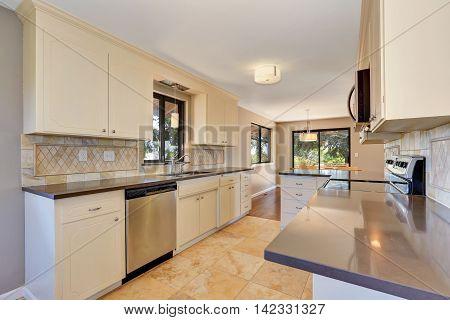 Kitchen Interior With Tile Back Splash Trim And Tile Flooring.