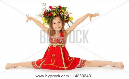 Beautiful little girl in a bright red dress with a large floral wreath on his head. Girl does the splits with his hand-Isolated on white background