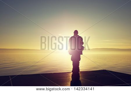 Old man as tourist with camera on Lake Constance at sunset silhouetted - nice sky and water