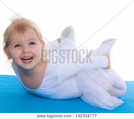 Gentle little girl , a future gymnast, white sports dress lying on blue track Mat-Isolated on white background