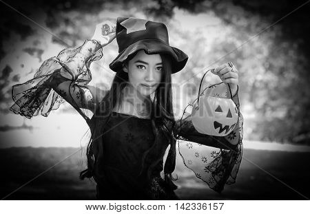 portrait of Asian woman on black dress and holding plastic pumpkin doll in garden Back and white Halloween concept