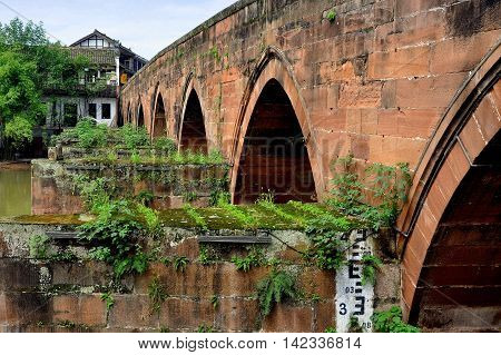 Ping Le Ancient Town China - September 28 2010: Coral-colored sandstone bridge with gothic arches spans a gently flowing river dividing the town into two districts