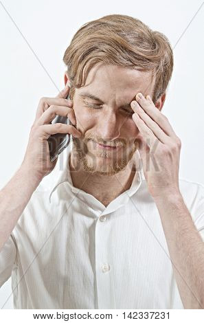 Young Adult Man in White Shirt Listening to His Phone, Touching His Head with a Hand, Receiving Bad News