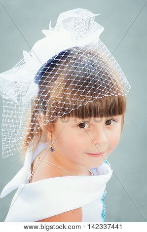 Portrait of a cute little girl in a magnificent white and blue dress