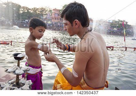 Ujjain Madhya Pradesh India - May 18 2016: A young priest paints the arm of a boy-apprentice before a fire ceremony called 'aarti' at the Kshipra River during the Kumbh Mela religious festival in Ujjain India on May 18 2016. Kumbh Mela is the largest even