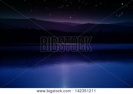 The night starry sky over the mountains and the lake