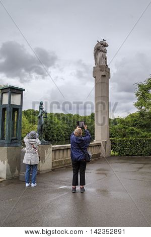 OSLO, NORWAY - JULY 1, 2016: Tourists take pictures in the memory of sculptures of all kinds of modern photographic equipment in the Vigeland Sculpture Park.