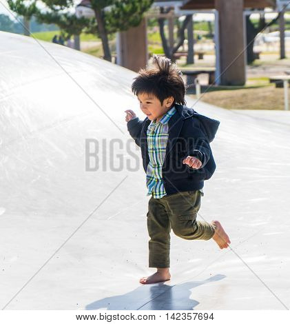 Japanese Boy Running in sun light playground