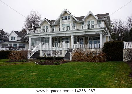 A large elegant home, with a front porch and balcony, on Beach Road in Wequetonsing, Michigan.
