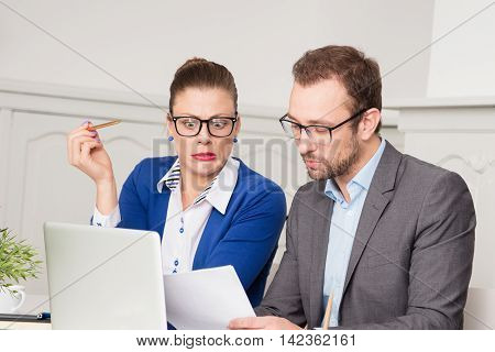 Businesswoman realized mistake on document during the meeting with boss. Business failure and stress concepts.