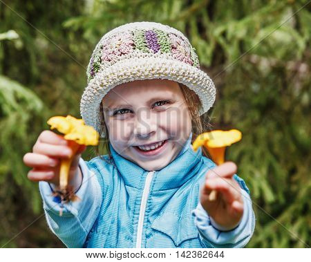 Portrait of smiling cute little girl with mushrooms in a park. Close-up of beautiful child, outdoors