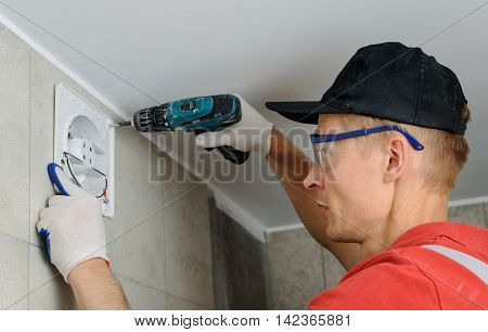 Installation of household appliances. Workman fixing the exhaust fan on the wall.