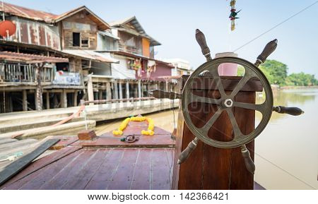 Thai River Boat wooden steering wheel with village background