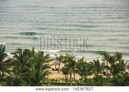 low season in tropical resorts and hotels, no tourists, empty beach beds, windy and stormy weather, China, Hainan