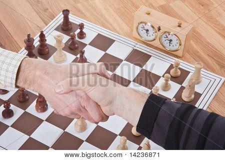 Händeschütteln durch ein Schach-Spiel