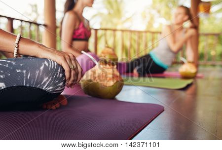 Woman Sitting At Yoga Class With Coconut