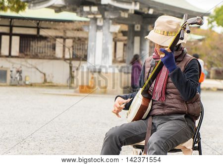 Osaka, Japan - March 11, 2016: Osaka castle on March 11, 2016. A Japanese musician is playing traditional music in Osaka park.
