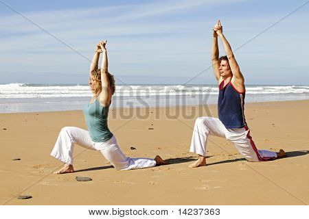 Young couple doing yoga exercises at the beach
