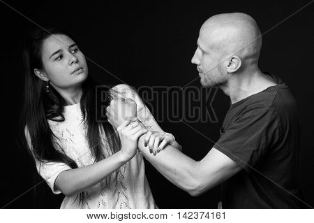 Domestic violence- a man fighting with a woman black and white