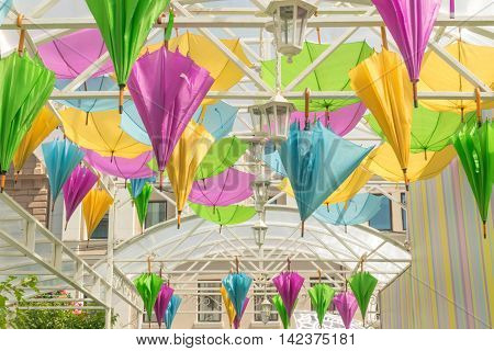 Street decorated with colored umbrellas. Colorful parasol. Summertime and rain.
