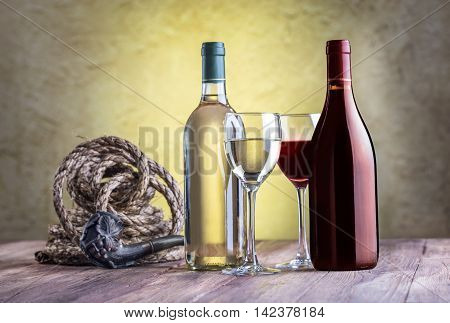 Still life with wine glass bottles rope and tobacco pipe on stucco background.