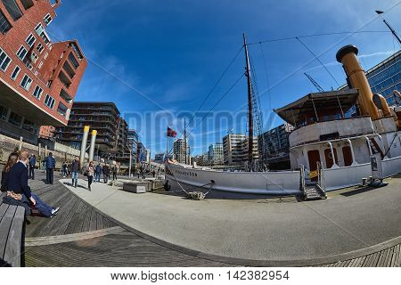 HAMBURG GERMANY - MARCH 26 2016: Fish eye view on modern buildings ships and visitors in the New Harbor City of Hamburg