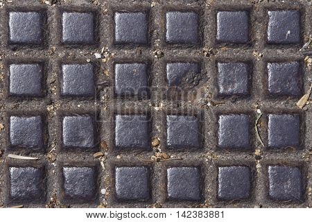 Old dark metal manhole texture with square pattern background macro selective focus.