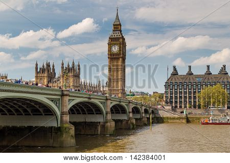 LONDON - MAY 10: London bus crossing Westminster Bridge near Parliament on May 10 2016 in London UK. London is one of the world's leading tourism destinations
