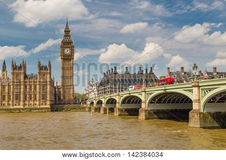 LONDON - May 07: London Buses with Big Ben on May 07 2016 in London England.