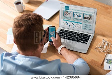 Write back. Pleasant busy man sitting at the table and holding cell phone while being involved in work