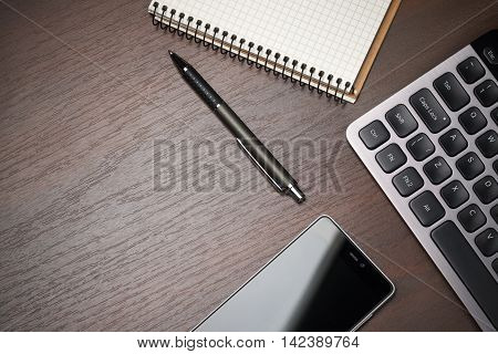 Business workspace desktop background with pen phone notebook and keyboard. Empty space top view