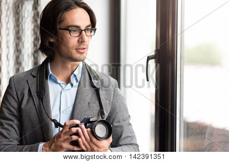Devoted photographer. Pleasant handsome man standing near window and holding photo camera