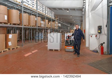 Worker Driving Goods in Warehouse With Pallet Truck