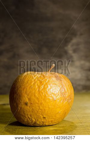 Rotten wrinkled apple on a wooden background