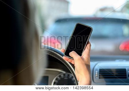 Young woman driver reading a text message on her mobile while driving her car in traffic close up view on her hand and phone with a view through the windscreen