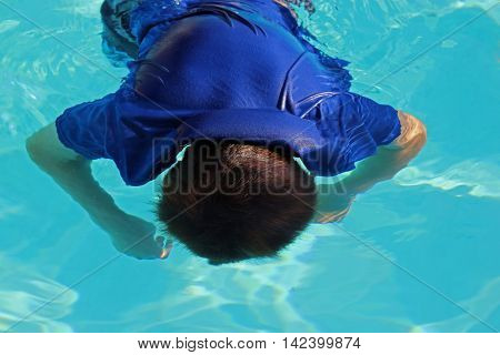 Boy child floating face down in pool as if drowned, released staged photo.