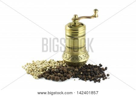 Pepper mill. Old oriental pepper mill and black pepper. Black peppercorns and black pepper powder.