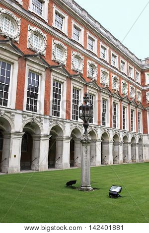 LONDON, ENGLAND - JUNE 14, 2014: Courtyard of Hampton Court Palace on June 14, 2014 in London, England. It is one of the most visited palaces in England.
