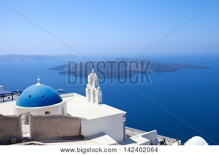 The Three bells of Fira and blue dome, Santorini, Greece with Santorini's volcano in the background