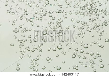 Many small beautiful golden air bubbles soars over a blurred background
