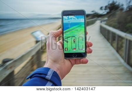 Male Hand Holding Iphone 6 With Pokemon Go On Boardwalk