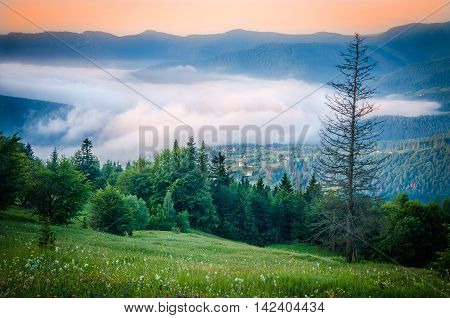 The village in the mountains. Mist covers the village in the mountains in the morning in the summer. Autumn fog in the mountains in the morning.