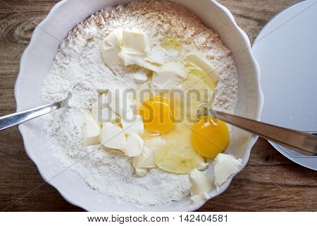 mixing eggs cake flour and butter in a ceramic bowl to preparing a sponge cake