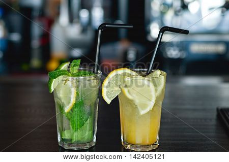 Two of refreshing lemonade with lemon and lime on a background of the bar in the cafe. Summer drink.