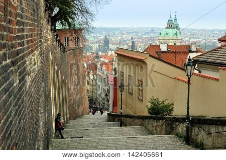 Prague, Czech Republic - April 11, 2016: Narrow street with stone staircase in Prague against the backdrop of the old town panorama. A street musician with guitar stands near the wall.